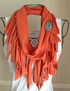 Light orange recycled/upcycled t shirt/jersey infinity fringe scarf/necklace with turquoise/sea coral metal brooch. My love for the sea/beach inspired this scarf/necklace. It is made from one recycled t shirt and a brooch, created from a pendant and a brooch pin. The scarf can be worn long or looped for a shorter/chunkier version. It looks great with a white t shirt or tank and is very lightweight. Throw on a light jacket/sweater for a dressier look. Love the colors on this scarf! $20.00.