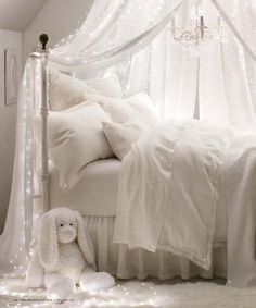 girls bedroom- all white bedding and canopy with twinkling lights.