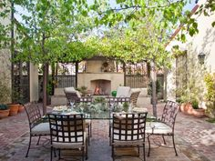 Designer Molly Wood created this Mediterranean courtyard that's ideal for outdoor entertaining. The stucco fireplace is the focal point of the room, and centering the dining table in front of it creates classic symmetry. Tour the rest of this amazing outdoor room now.