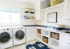 White and blue laundry room features a white front load washer and dryer placed under windows dressed in a turquoise chevron roman shade situated beside stacked floating shelves filled with laundry detergents.