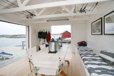 love the simple plank-style table, exposed trusses, doorwall that opens completely to the water....boathouse