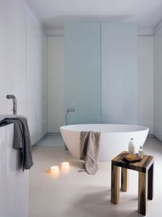 The tub is plopped in the middle of the room, with the cloudy glass wall of the shower/toilet area as a backdrop.