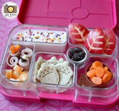 an adorable Fall bento for Kirsten in her pink yumbox. This was really fun to make! The protein section has turkey bologna roll-ups with with squirrel and acorn picks and cubed marble cheese. The grains section has acorn-pressed bread pieces. The veggie section has a cute squirrel silicone cup with sliced baby carrots. The dairy section has yogurt with cute fall leaf sprinkles. The fruit section has slices of red apple that I carved to look like fall leaves, and I put some raisins in the…