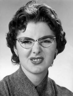 Unknown. But I love the whole package—hair, glasses, blouse. I imagine she's reacting to me telling her I think she's beautiful.