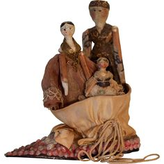 Three primitive Grodnertal dolls in a shell shoe from sarah-sellers on Ruby Lane