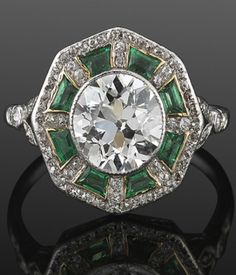 An early Art Deco diamond and emerald ring, circa 1915. An old European cut diamond is surrounded by calibré emeralds and single cut diamonds set in platinum. #ArtDeco #ring