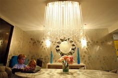Lara Spencer's dining room: Spencer found the chandelier -- strings of glass balls -- at   Interior Illusions  . The mirror is from    Z Gallerie  . The 1960s chrome sconces on both sides are from   1stdibs.com  .