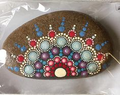 An original hand painted mandala stone in vibrant colors. Each stone is sealed with an acrylic spray and comes with a card explaining the history of the good fortune mandala stone. Mandela Rock Painting, Stone Art Painting, Dot Art Painting, Mandala Painting, Pebble Painting, Pebble Art, Rock Painting Patterns, Rock Painting Ideas Easy, Rock Painting Designs
