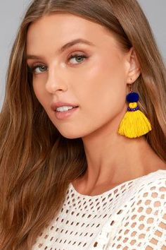 """Add a pop of fun with the Shashi Emily Blue and Yellow Tassel Earrings! Bright yellow threaded tassels dangle beneath royal blue pompoms with matching beads. Earrings measure 3""""."""