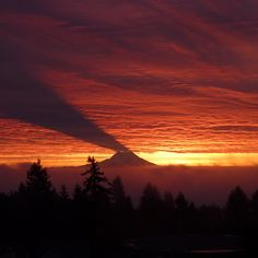 """Mt. Rainier, Washington. """"Usually it's the clouds that cast a shadow on the ground, not the other way around. Wednesday morning, Seattle area residents were treated to this spectacular sunrise as the first rays of light hit Mount Rainier before reaching the sky."""""""