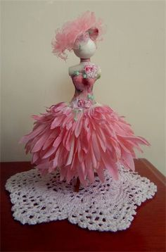 Exquisite silk petal designer dress on dainty resin mannequin 5 inches tall (1/12th scale). Rose design bodice and beautiful embroidered varigated pink and white roses . The skirt is formed from very delicate pink silk hand layered petals.Gown comes complete with soft pink organza petal hat.