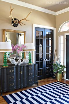 Front Entry // striped rug, antlers, oversized clam shell, brass, fiddle leaf fig, black doors