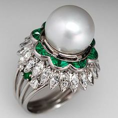 This stunning vintage South Seas pearl cocktail ring features a near round pearl prong set into a dual halo of triangle cut natural emeralds, set back-to-back creating a scalloped effect, and a lower halo of marquise cut natural diamonds. Accenting the domed area of the ring, set onto a wire shank, are round diamonds and emeralds.