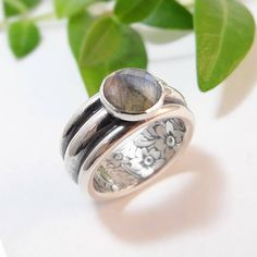 One of my favorite designs! A wide sterling silver band with an 8mm checkerboard-faceted blue/green labradorite stone set on top. The ring features a hefty band that measures just under 9.5mm wide and is built from three stacked half round tiers (two thinner tiers framing one