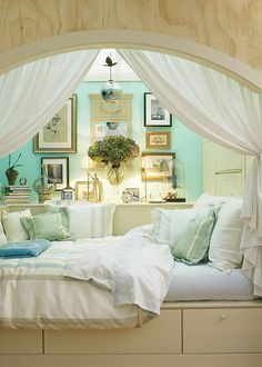 Neat the way the bed is between rooms.  I like the canopy, turquoise, flowers hanging on the wall