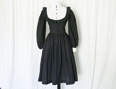 Vintage dress from the 1950s in black and white featuring tuxedo pleated bib collar and black and white polka dot balance. There is a ruffle around the bib and black buttons down the front. The sleeves are long and puffed with white cuffs. The bodice is fitted, the waist has a little give, and the skirt is very full with hidden hip pockets.  Modern Sizes: XS to S Label: Lemington Fabric: Cotton Condition: No flaws; excellent vintage condition: no stains, no holes.  Measurements in inches…