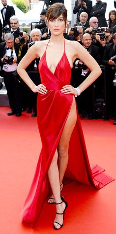 Bella Hadid killed it at The Unknown Girl premiere during #Cannes in a custom red silk Alexandre Vauthier Couture wrap gown that had a down-to-there plunge and a racy waist-high slit. Teardrop earrings and black strappy Giuseppe Zanotti sandals completed her look. #Celebrity