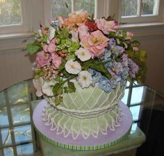 This garden wedding cake was created for a television segment on new trends for wedding cakes for the series Party Planner with David Tutera soon to be airing on the Discovery Home Channel.  A French wire basket cake in sage green and white is virtually overflowing with a myriad of sugar flowers including hydrangeas, morning glories, roses, leaves, wildflowers and berries in a pastel color palette.