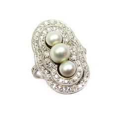 Early 20th century three stone pearl and diamond cluster ring, c.1905  , the graduated pearls set vertically within a shaped double border of diamonds, millegrain set in platinum, diamonds to the shoulders