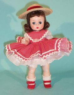 """Blossom Doll - 1From Spring, 1954, comes this striking dark-haired straight leg walker Wendy (#560) who shines in red - """"red slippers, red streamers on her hat, and a frilly pinafore of red pin dot cotton trimmed with braid, add glamour to her fine white organdie dress. Lingerie of white organdie, lace edged."""