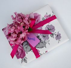 Beautiful floral giftwrap, bright pink ribbon and millinery flowers to top!