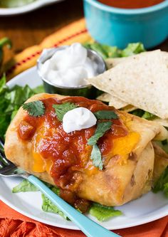 Beef Chimichangas Recipe - RecipeChart.com -- 1 pound lean ground beef ½ cup diced onion 1 garlic clove, minced 1 teaspoon chili powder ½ teaspoon cumin ½ teaspoon dried oregano 1 (15-ounce) can refried beans 1 (8-ounce) can tomato sauce 1 (15-ounce) can tomato sauce 1 (4.5 ounce) can green chilies 1 jalapeno, minced 8 (10-inch) tortillas wooden toothpicks 1½ cups shredded Cheddar cheese or Colby Jack Vegetable oil Cilantro and sour cream for garnish