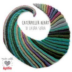 Laura Soria ha voluto apportare alcune modifiche ad un modello di scialle Caterpiller Heart, un semplicissimo lavoro a ferri adatto anche alle principianti.