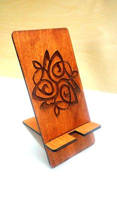 Wooden phone stand with engraved ornament.  - Dimensions 12cm(4.7Inch) X 16cm ( 6.2 Inch) - Material: wood 3mm - painted with walnut paint.