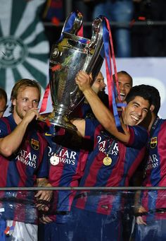 Luis Suarez of Barcelona lifts the trophy as he celebrates victory with team mates after the UEFA Champions League Final between Juventus and FC Barcelona at Olympiastadion on June 6, 2015 in Berlin, Germany.