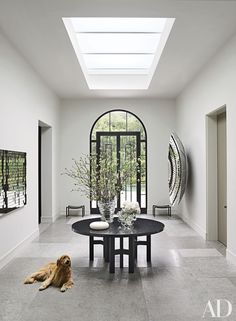 In the central hall of a Northern California home, the skylight brightens an Ado Chale table from Hedge. The owner's golden retriever lies on a floor of limestone.