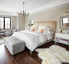 Chic French bedroom features blush pink bed dressed in white and pink bedding, white flokati pillows and salmon pink lumbar pillows flanked by white, French mirrors over white lacquered nightstands with shelf topped with faceted glass table lamps with linen shades alongside long, gray tufted ottoman placed at foot of bed.