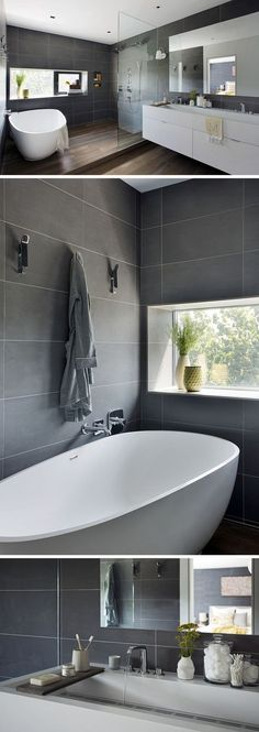 Large, dark grey rectangular tiles and wood flooring give this master bathroom a sophisticated look. The stand alone tub and shower area are slightly elevated above the rest of the room, with a glass partition separating the shower from the white vanity.