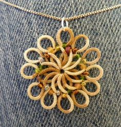 Tatted by IdahoCanuck, from her album: Tatting 2013. Directions in the comments Swirl pendant PQ 'Sahara' thread with assorted glass beads. I saw a picture of something similar on a web page somewhere but don't know who...