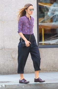 Keira Knightley wears a floral button-down, cuffed trousers, a quilted bag, round sunglasses, and oxfords