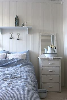 cozy farmhouse look....white paneled walls..white shelf over bed..mirror and night stand...