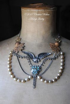 This necklace is so full of character and a real statement maker. It features a silvertone eagle as its centerpiece and it is accented with vintage rhinestone chain, an art deco rhinestone tassel necklace, vintage Haskell era pearls, vintage scrolled connector pieces, and a pair of vintage gold tone former clip-on earrings that resemble old military badges. This necklace looks amazing worn with anything from a tank top t-shirt to a dressy silk collar blouse! This one of a kind necklace…