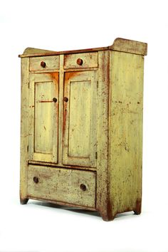 """American, mid 19th century, pine and poplar. Two drawers over door doors over one long drawer, with a gallery. Retains old, worn yellow paint over earlier red. 58.25""""h. 43""""w. 20.25""""d."""