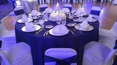 A wedding reception held in our Grand Ballroom for just under 100 guests. This wedding featured blue uplighting, our lantern & hydrangea centerpiece, navy table cloths for guest tables, white spandex chairs with a satin navy sash tied in a bow, silver chargers, white napkins in a fan fold and silver sequin linen accents!