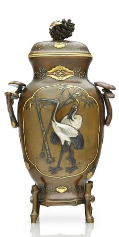A soft-metal-inlaid bronze jar with cover  Meiji period (late 19th century)  Of ovoid form with a short neck, applied with two handles cast in the form of auspicious fungus, inlaid in gold, silver, copper, gilt and shakudo with two panels designed with cranes and bamboo, the body set on bamboo feet and the lid with a pine cone finial applied with a butterfly 13¼in. (33.7cm.) high