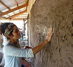 Photo by Werner Elmker. Sustainable living student slapping mud on a strawbale house in Fairfield, Iowa