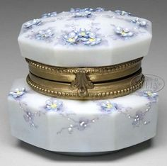 glass, Connecticut, A Nakara [glass dresser] octagonal box decorated with tiny applied blue flowers with white enameled specks in the center of each petal and a yellow enameled dot in the middle of each flower. Flowers are connected by subtle purple stems and leaves with white enameled dot highlights. All the decoration is set against a light blue background, [hinged lid]. Signed on bottom Nakara C.F.M. Co.