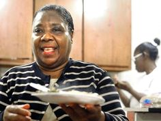"""Pastor Dorothy Wilson of the New Beginnings Church of Deliverance takes a plate of food to a visitor at the church, which serves free meals to the public from 10 a.m. to 2 p.m. weekdays. """"We serve real food. Soul food,"""" Wilson said. The church will be offering free meals """"as long as we can."""""""