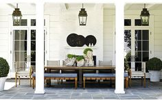 Bunny Williams--love the lanterns, the slate blue covers on benches that coordinate with slate flooring and the boxwood!