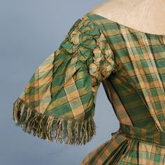 GREEN PLAID SILK EVENING DRESS, MID 19th C. 2-piece taffeta, boned bodice having open neckline with drawsting at back, short fringed bell sleeve with three rows of ruching at the shoulder, linen lining. Full skirt with pleats having hem with braided binding and backed with a band of polished cotton. Together with a single matching button-on long bell sleeve.