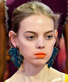 Windswept updos and neon lipstick, like this model's orange matte shade.