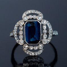 An early Art Deco platinum ring, circa 1915, centered with a natural blue sapphire set in a scalloped openwork frame embellished with old single and rose cut diamonds.