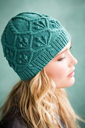 Cabled cap worked in the round with floral cabled details and ribbed brim. Sized for adult woman and shown on page 60.