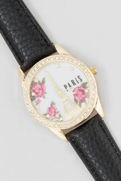 """Get a taste of Paris with the Le Paris Eiffel Tower Watch! The gorgeous watch features a gold crystal bezel, textured black band and a lovely Eiffel tower background with pink roses and gold hearts at each hour. Wear alone or with gold bangles for a trendy stacked look.<br /> <br /> - 1.5"""" face<br /> - Imported"""