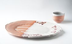 Decorative, handmade ceramic plate with white glaze, terra sigillata and lithographic floral design. Wheel thrown cup with white glaze and terra sigillata. Made by Ingrid Wens.