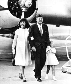 President Kennedy and Caroline holding hands as they and Mrs. Kennedy walk from the plane that returned the President's wife and daughter from a vacation in Italy, 1962.